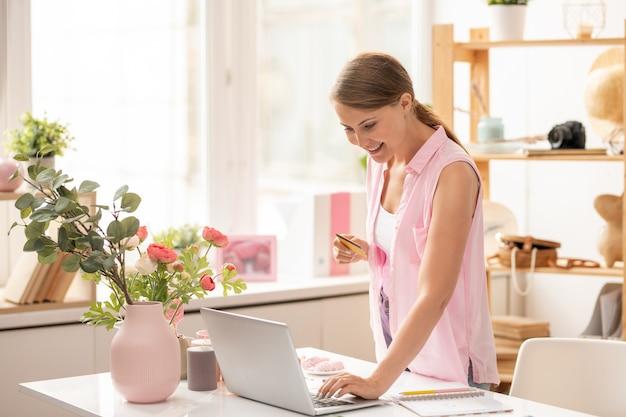 Jolie jeune femme en tenue décontractée entrant des données financières ou le nombre de cartes en plastique lors de vos achats en ligne