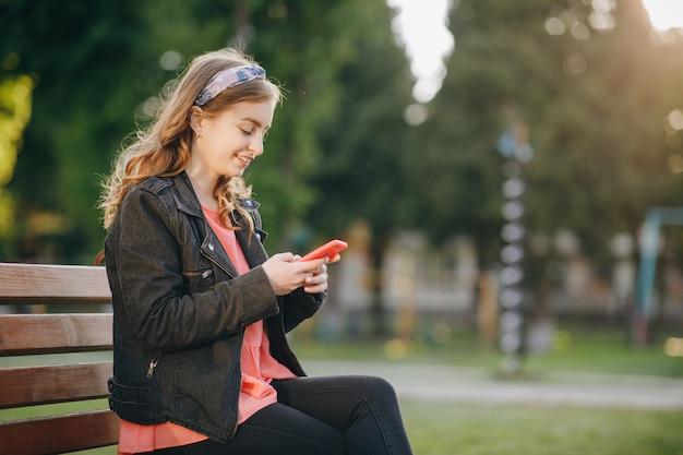Jolie jeune femme en tenue décontractée à la mode est assise sur un banc dans le parc de la ville. être en ligne, technologies modernes
