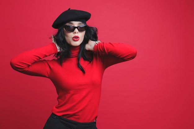 Jolie jeune femme en tenue élégante grimaçant et touchant les cheveux en se tenant debout sur fond rouge vif
