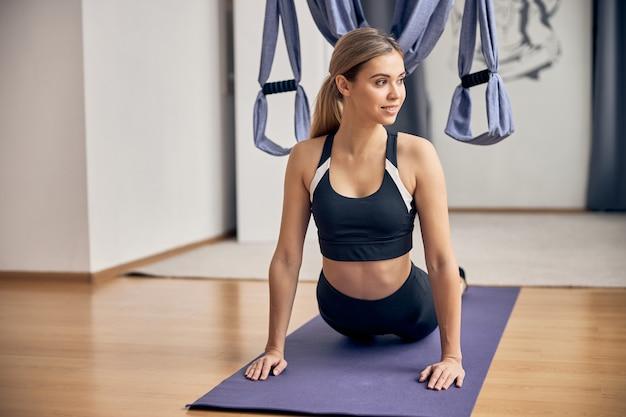 Jolie jeune femme en tenue de sport faisant de la gymnastique sur le tapis de yoga violet et souriant