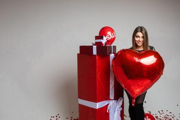 Jolie jeune femme tient un ballon à air dans ses mains et se tient près de cadeaux, photo sur blanc