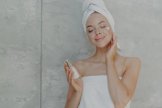 Jolie jeune femme tient une bouteille de lotion pour le corps, applique la crème pour le visage sur le teint