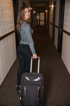 Une jolie jeune femme tirant le sac de bagages à pied dans le couloir de l'hôtel