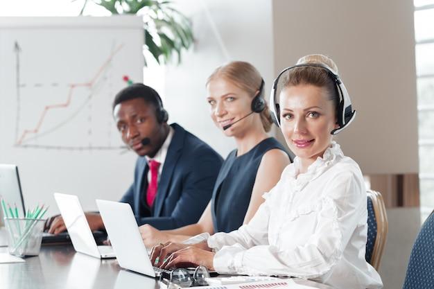 Jolie jeune femme travaillant dans un centre d'appels avec ses collègues