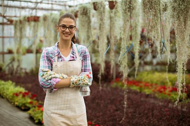 Jolie jeune femme travaillant avec des fleurs de printemps en serre