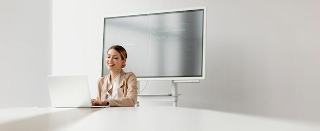 Jolie jeune femme travaillant sur ordinateur portable au bureau lumineux avec grand écran derrière elle