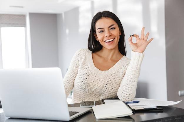 Jolie jeune femme travaillant avec un ordinateur portable et des documents alors qu'elle était assise à la cuisine, ok