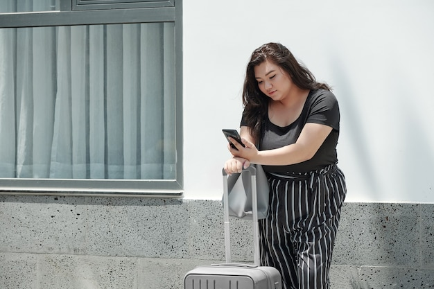 Jolie jeune femme utilisant l'application sur smartphone lors de la commande d'une voiture de taxi à la gare ou à l'aéroport