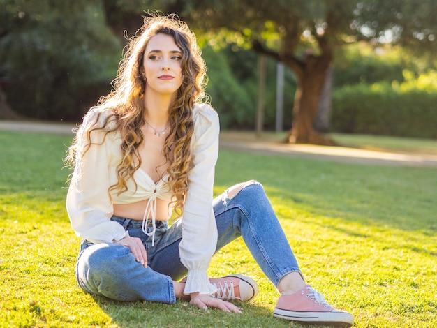 Jolie jeune femme en vêtements décontractés passant du temps libre dans le parc du printemps