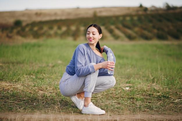 Jolie jeune femme en vêtements de sport avec une bouteille d'eau