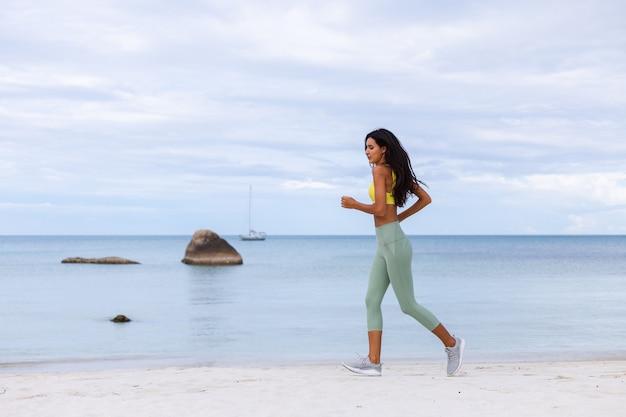 Jolie jeune femme en vêtements de sport colorés sur la plage
