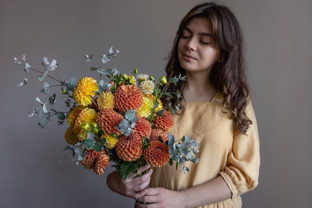 Jolie jeune femme vêtue d'une robe jaune avec un bouquet de chrysanthèmes lumineux sur fond gris.