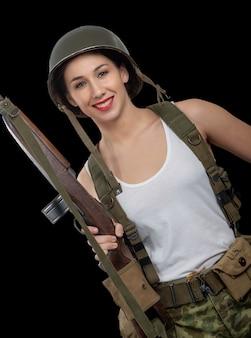 Une jolie jeune femme vêtue de l'uniforme militaire américain de la seconde guerre mondiale avec casque et fusil