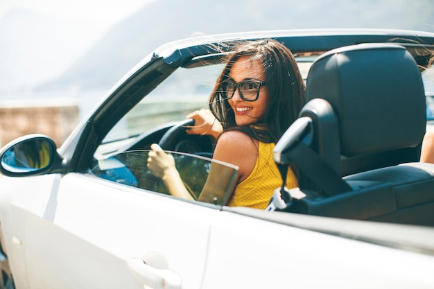 Jolie jeune femme en voiture blanche cabriolet