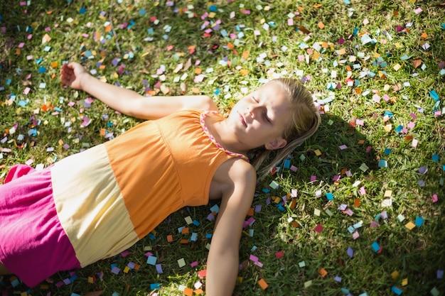 Jolie jeune fille allongée sur l'herbe dans le parc