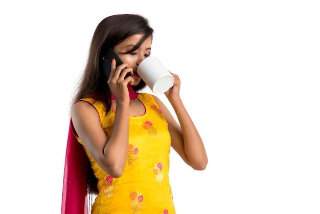 Jolie jeune fille appelant sur un appareil smartphone tout en buvant une boisson savoureuse de café ou de thé