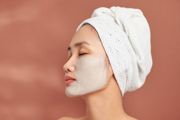 Une jolie jeune fille asiatique avec une serviette blanche sur la tête a appliqué un masque d'argile utile