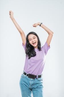 Jolie jeune fille asiatique souriant joyeusement à la recherche tout en serrant les poings et levant les deux mains