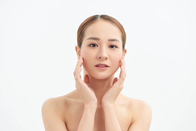 Jolie jeune fille asiatique touchant son visage sur fond blanc. concept de beauté et de soins de la peau