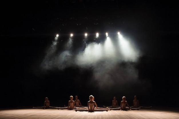Jolie jeune fille assise sur scène ayant des étirements et une formation pour la danse classique.