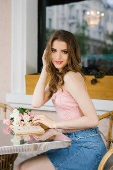 Jolie jeune fille assise à une table dans un café dans la rue, tenant un livre dans ses mains et souriant