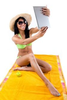 Jolie jeune fille au bikini vert prenant des selfies avec sa tablette numérique