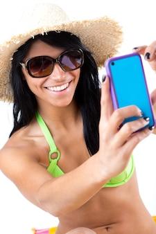 Jolie jeune fille au bikini vert prenant des selfies avec son téléphone intelligent