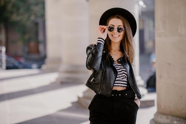 Jolie jeune fille aux cheveux bruns français dans une veste en cuir, chapeau noir sur la promenade de la ville
