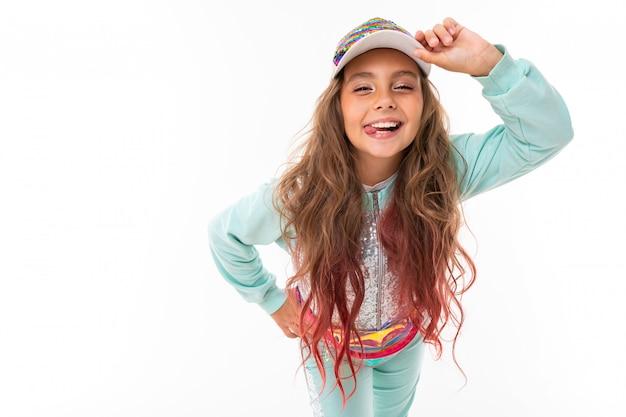 Jolie jeune fille aux cheveux longs avec un costume de sport décontracté et une casquette de baseball sur fond blanc
