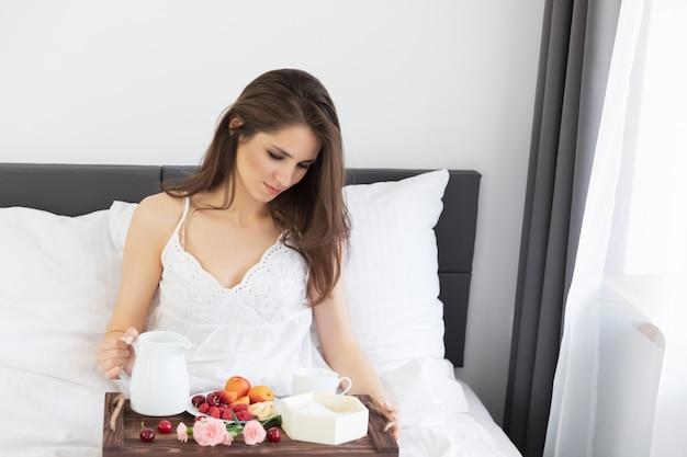 Une jolie jeune fille aux cheveux longs est assise dans un peignoir blanc sur le lit.