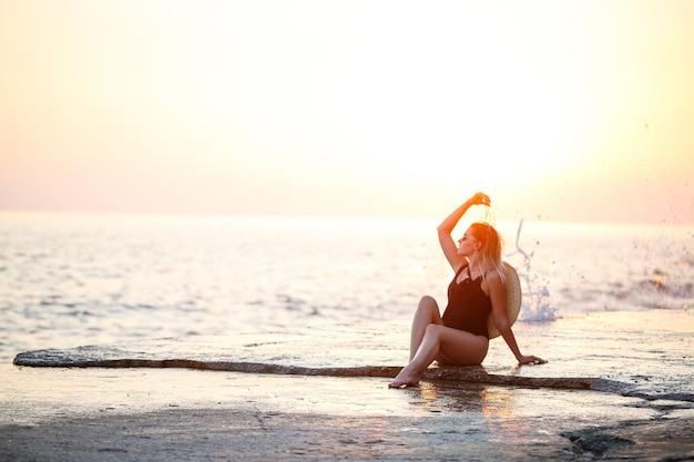 Jolie jeune fille aux cheveux longs pose devant la caméra sur la plage. elle porte un maillot de bain noir. lumière dorée du coucher du soleil. mise au point sélective