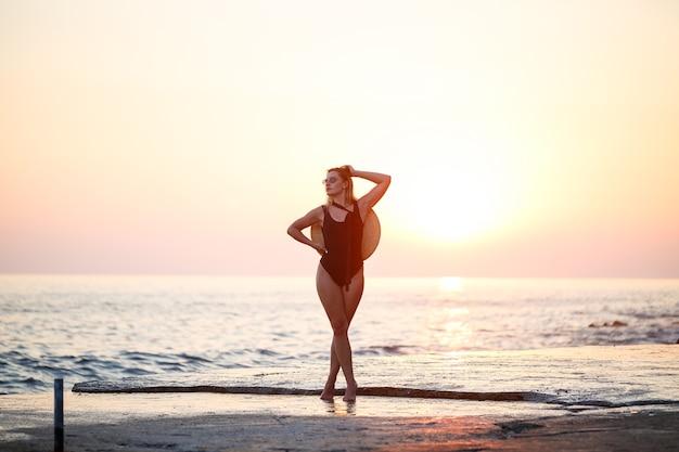 Jolie jeune fille aux cheveux longs pose devant la caméra sur la plage. elle porte un maillot de bain noir. lumière dorée du coucher du soleil