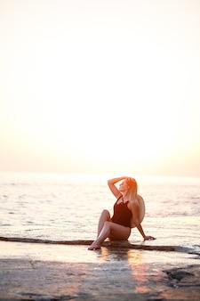 Jolie jeune fille aux cheveux longs pose sur la plage. elle porte un maillot de bain noir. lumière dorée du coucher du soleil