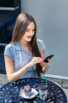 Jolie jeune fille aux cheveux longs utilisant un smartphone dans un café en plein air