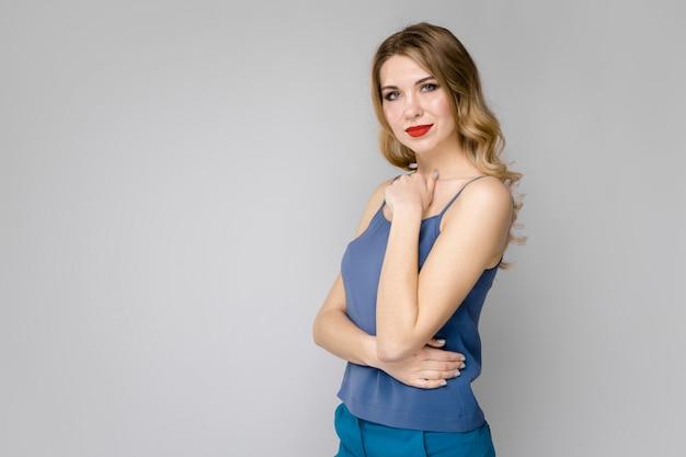Jolie jeune fille blonde en vêtements bleus sérieux confiant