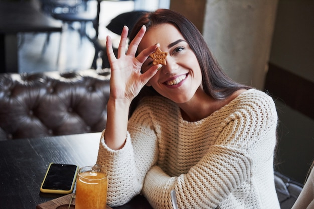Jolie jeune fille brune détient le cookie en forme d'étoile avec inscription qui signifie meilleurs voeux