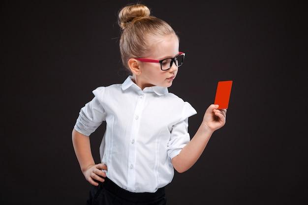 Jolie jeune fille en chemise blanche et un pantalon noir tiennent un carton rouge