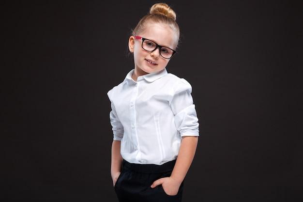 Jolie jeune fille en chemise blanche et pantalon noir