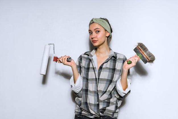 Jolie jeune fille en chemise à carreaux tenant un pinceau et un rouleau pour peindre les murs, ne peut pas choisir