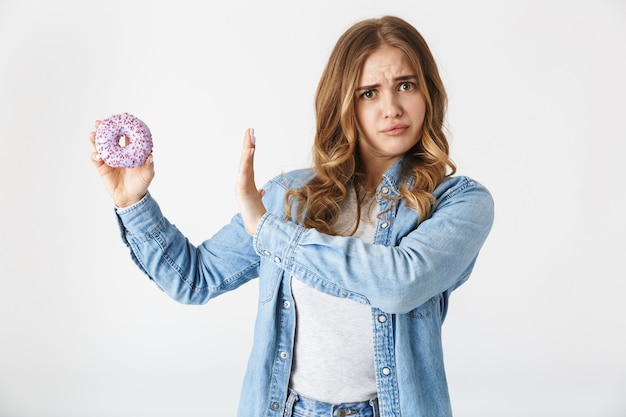Jolie jeune fille confuse debout isolée sur blanc, tenant un beignet savoureux