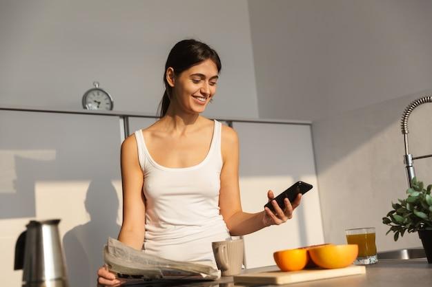 Jolie jeune fille debout dans la cuisine le matin, ayant une tasse de café, à l'aide de téléphone mobile