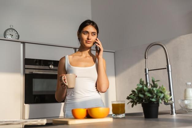 Jolie jeune fille debout dans la cuisine le matin, ayant une tasse de café, parler au téléphone mobile