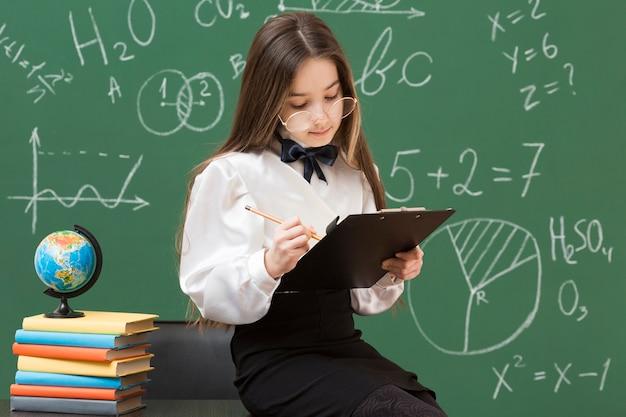 Jolie jeune fille écrivant dans le presse-papiers