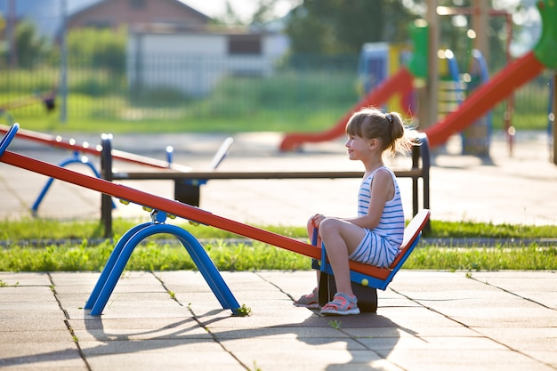 Jolie jeune fille enfant à l'extérieur sur une balançoire à bascule sur une journée d'été ensoleillée.
