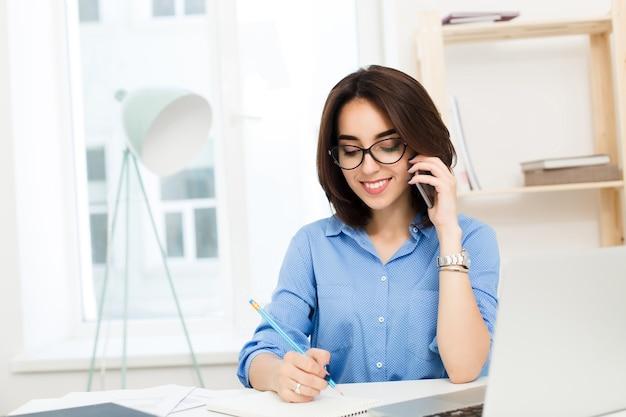 Une jolie jeune fille est assise à la table au bureau. elle a une chemise bleue et des lunettes noires. elle parle au téléphone et écrit sur un cahier.