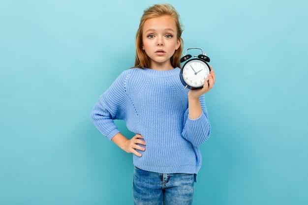 Jolie jeune fille européenne montre le réveil sur le mur bleu clair