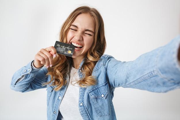 Jolie jeune fille excitée debout isolée sur blanc, prenant un selfie, montrant une carte de crédit en plastique