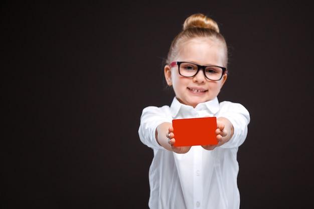 Jolie jeune fille gaie en chemise blanche et un pantalon noir tiennent un carton rouge