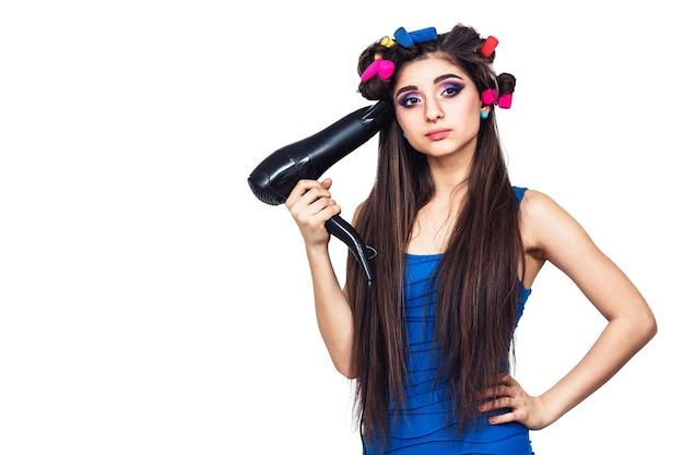 Jolie jeune fille gaie en robe bleue avec des bigoudis dans ses cheveux et avec un sèche-cheveux à la main. isolé sur une surface blanche