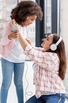 Jolie jeune fille jouant avec sa mère à la maison